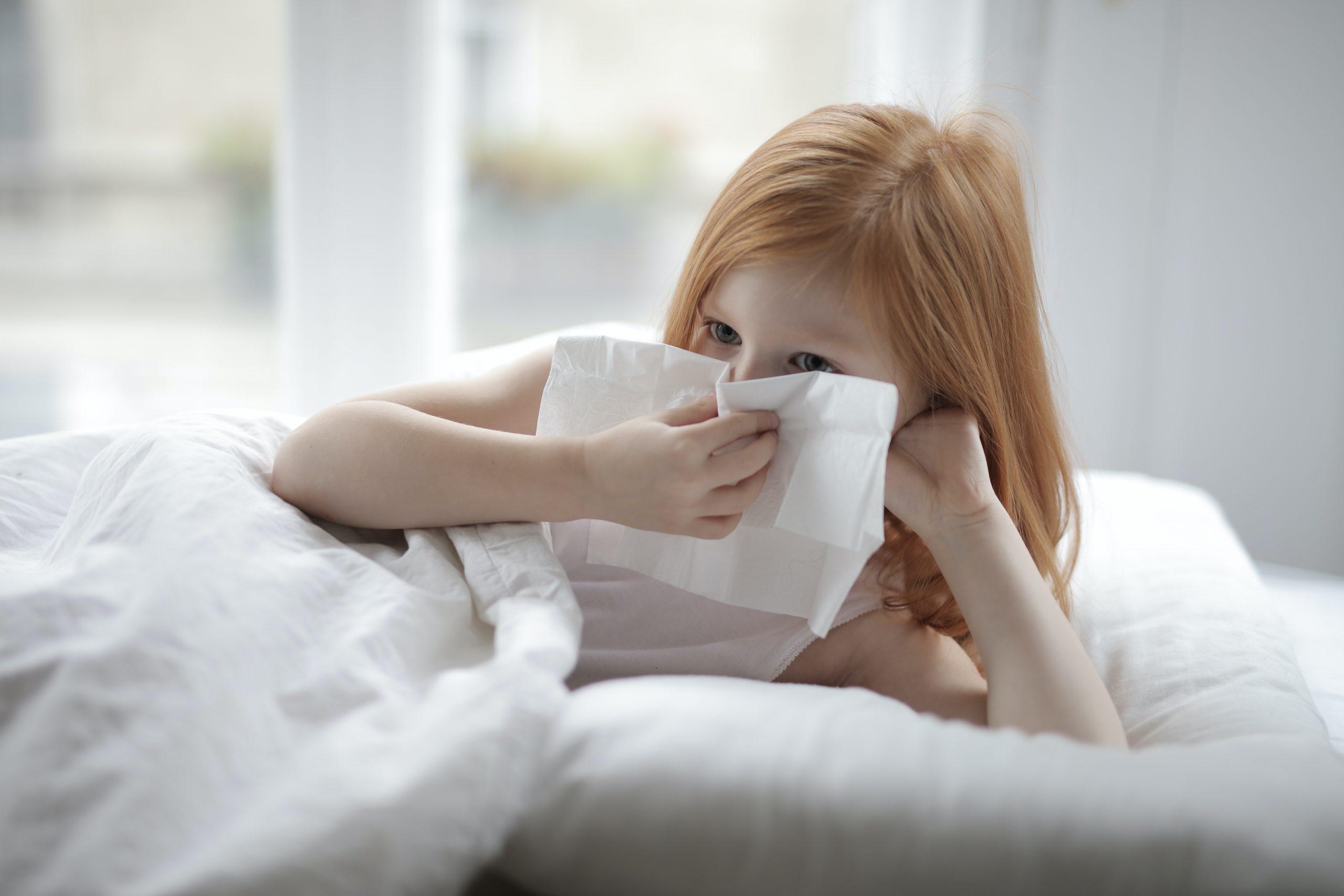 Ozonowanie zabija roztocze kurzu domowego i pomaga na alergie - na obrazku widać rudą dziewczynkę leżącą w łóżku z chusteczką w ręce