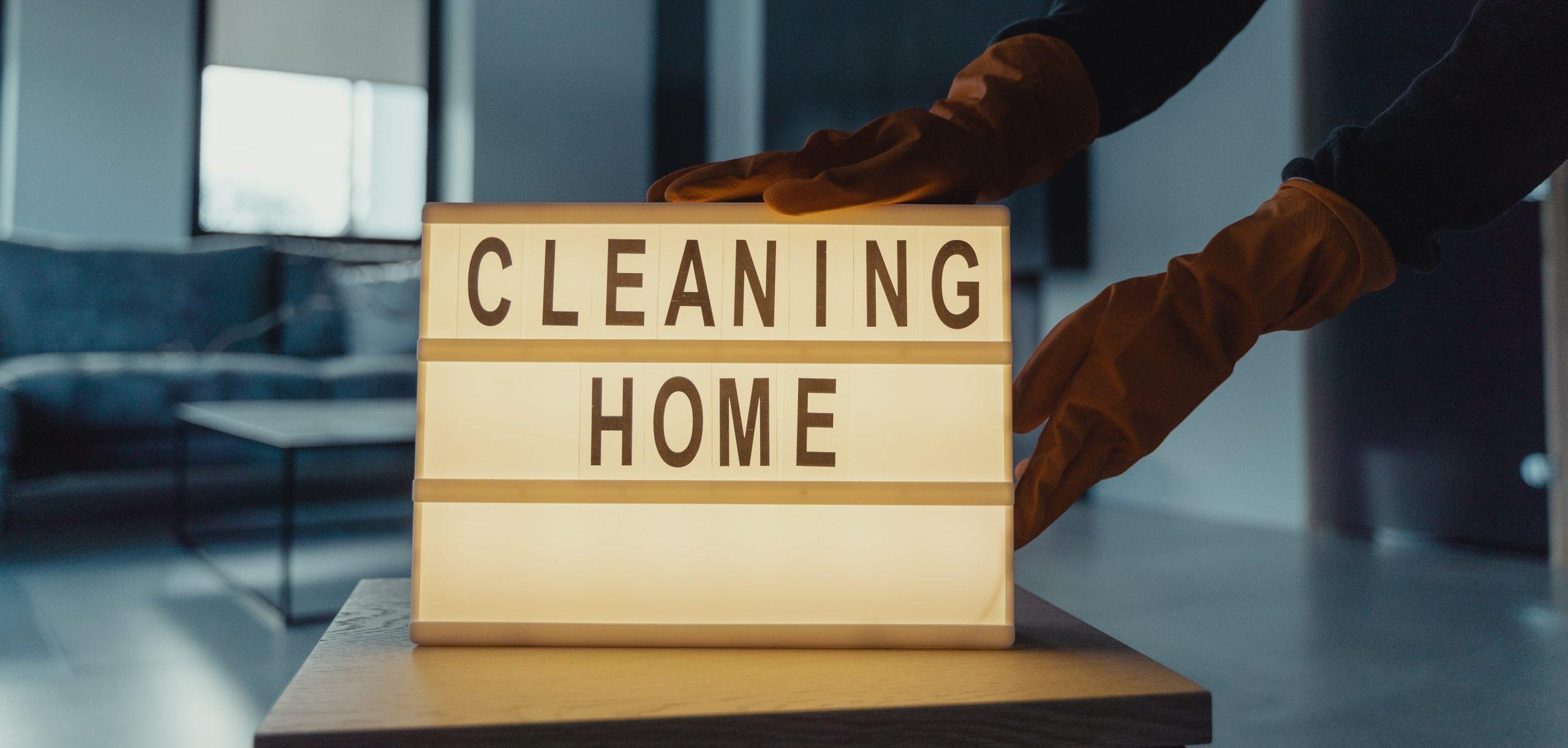 Banner dla artykułu na temat ozonowania - na obrazku widać tabliczkę z napisem cleaning home stawianą na stole przez osobę w pomarańczowych rękawiczkach