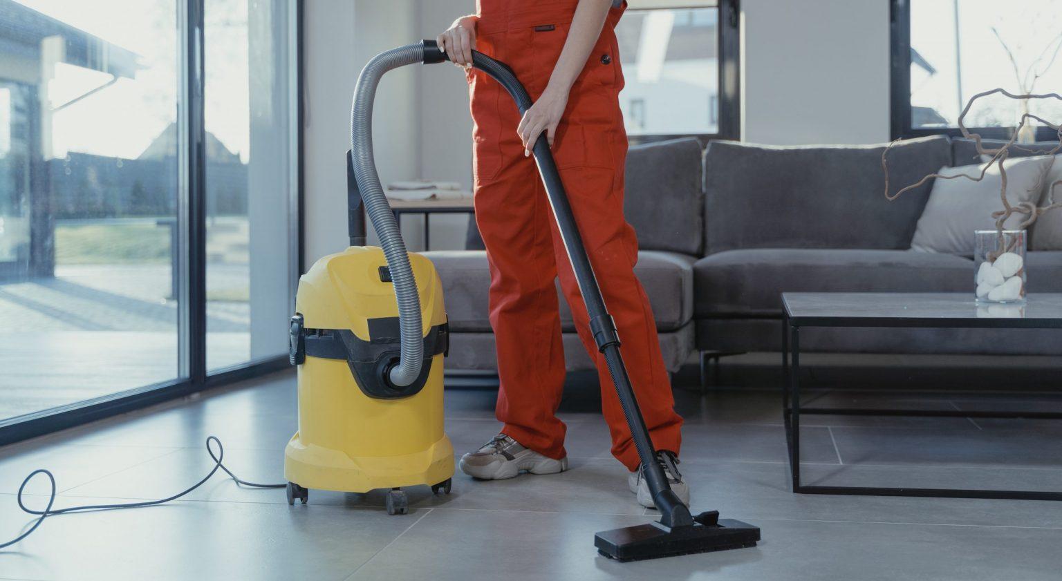 pranie tapicerek i tkanin metodą ekstrakcyjną - banner - kobieta w pomarańczowym stroju odkurzająca podłogę obok niej stoi żółty odkurzacz